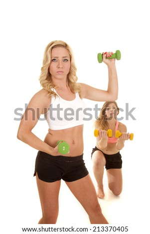 Two women working out with weights gaining muscle.