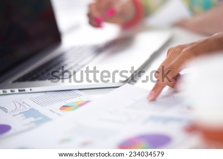 Two women working together at office, sitting - stock photo