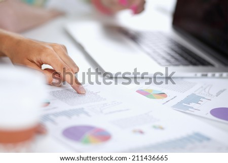 Two women working together at office, sitting on the desk - stock photo