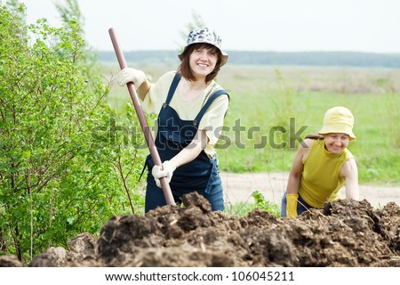 Two women works with animal manure at field