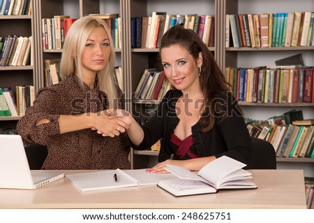 Two women young employee of the office and the student on probation. Women work together. Female business. To agree to come to terms with each other. Make the right decision. Practice in the office. - stock photo