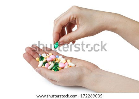 Two womens hands hold color pharmaceutical pills, isolated on white