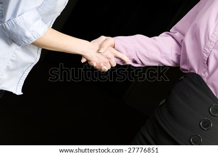 two womens hands shaking or grasping each other - stock photo