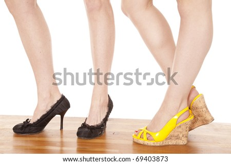 Two womens legs facing to the left. - stock photo