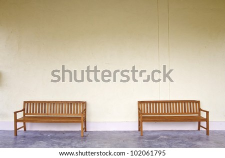 two wood Benches Against blank Wall.