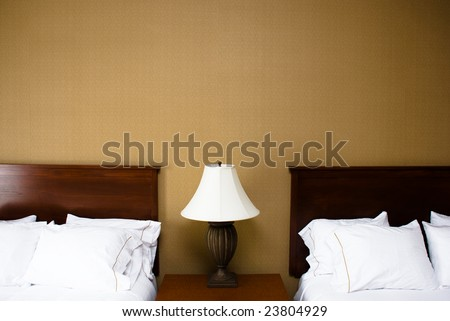 Two wood headboards and white fluffy pillows on either side of a lamp with white lampshade on a wooden bedside table top.  Beige plain wallpaper is on the wall behind the beds. - stock photo