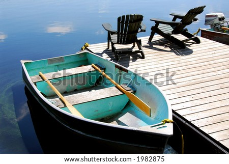 Two wooden adirondack chairs on a boat dock on a beautiful still lake with sky reflection - stock photo