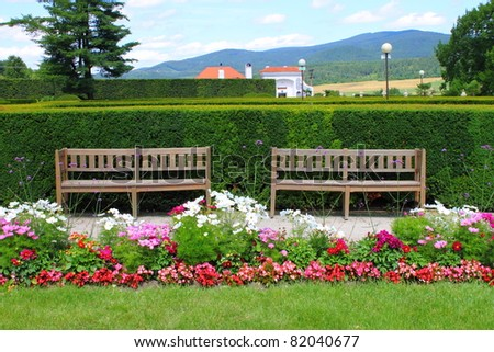 Two wooden benches in a beautiful park garden - stock photo