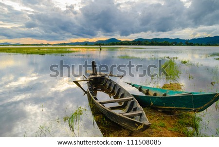 Two wooden boats are anchored, late afternoon on the Lak lake, Dak Lak, Central Highlands of Vietnam - stock photo