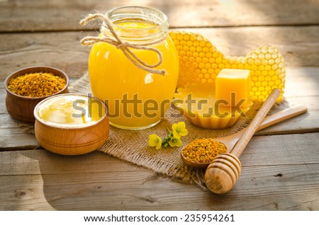 two wooden bowls one with honey another with pollen.The bank of honey stay near honeycombs,wax,wooden spoon with honey and dipper - stock photo