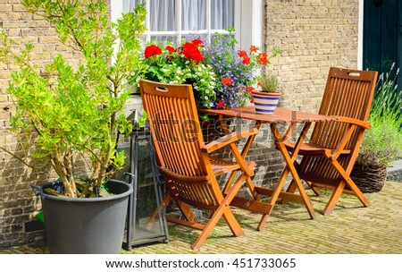 Two wooden chairs and a small table before the historic facades of the Begijnhof in the Dutch city of Breda. - stock photo