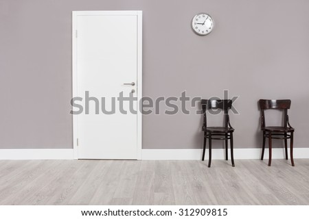 Two wooden chairs in a waiting room with a clock hanging on the wall above them - stock photo