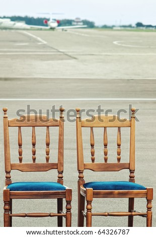 Two wooden chairs on airfield for VIP with blurred private jet in background - stock photo