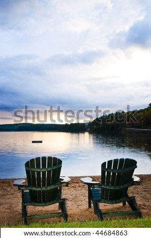 Two wooden chairs on beach of relaxing lake at sunset - stock photo