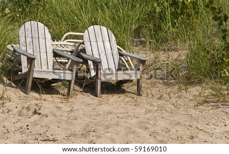 Two wooden chairs on the beach - stock photo