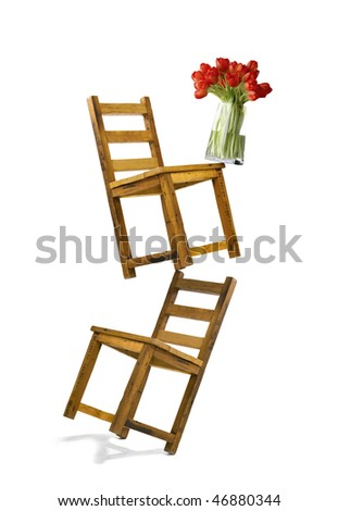 two wooden chairs , one above the other, and a vase with tulips in perfect balance. - stock photo