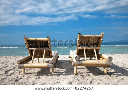 Two wooden deckchairs on an empty beach in Gili islands, Indonesia