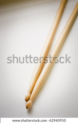 Two wooden drum sticks from above on a pale background