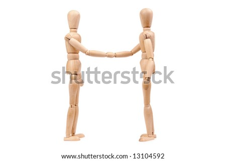 Two wooden dummies shaking hands over white background - stock photo