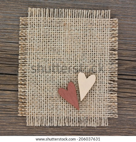 Two wooden hearts on canvas on old wooden background - stock photo