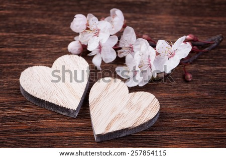 Two wooden hearts placed nicely with spring cherry blossom flowers on a vintage wood background - stock photo
