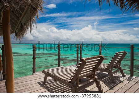 Two wooden lounge chairs sitting on the deck of an overwater bungalow suite overlooking the lagoon of a tropical paradise in Tikehau, Tahiti. - stock photo