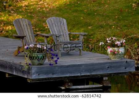 Two wooden Muskoka chairs on a dock