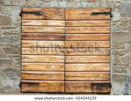 Two wooden shutters closed over window in stone wall