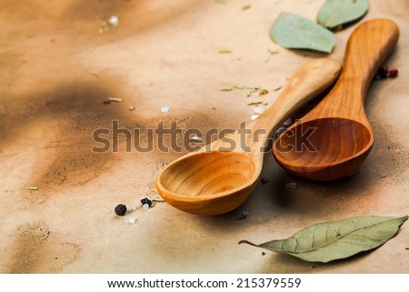 two wooden spoons, bay leaves, pepper and sal on old medieval paper - stock photo