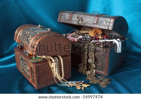 Two wooden treasure chests with valuables on blue textile - stock photo