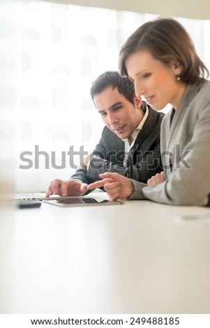 Two work colleagues, a young man and woman, analysing information or a report on a tablet computer as they sit together at a desk working, side view with copyspace. - stock photo