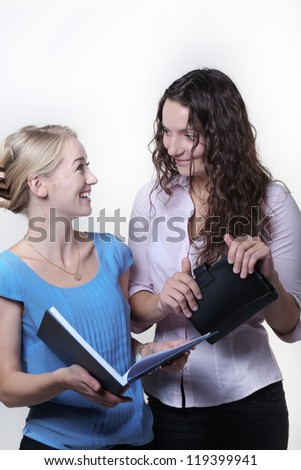 two work colleagues looking over something in a large note book, one woman is laughing out loud having fun