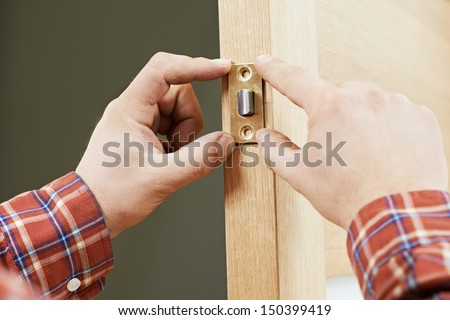 Two worker hands of carpenter at lock installation into wood door - stock photo