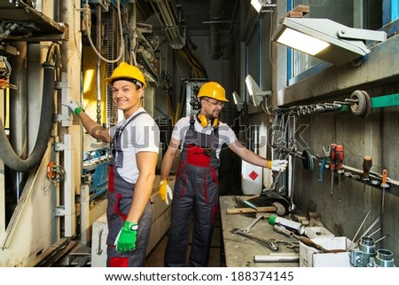Two worker in a safety hats  on a factory near near machine  - stock photo