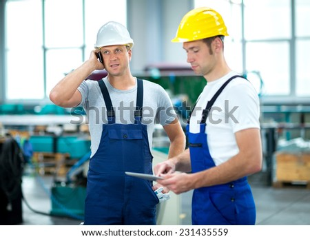 two worker in factory - stock photo