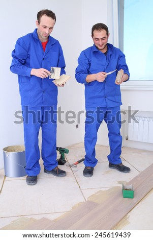 Two workers apply glue to the board for floor with a spatula in white room - stock photo