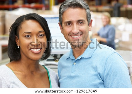 Two Workers At Computer Terminal In Distribution Warehouse - stock photo