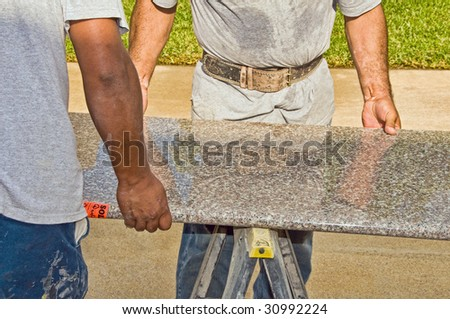 Two workers carry a large slab of granite into place - stock photo