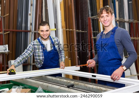 Two workers checking PVC window profile at stand. Focus on right man - stock photo