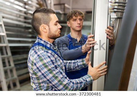 Two workers choosing PVC  aluminium window profile at stand - stock photo