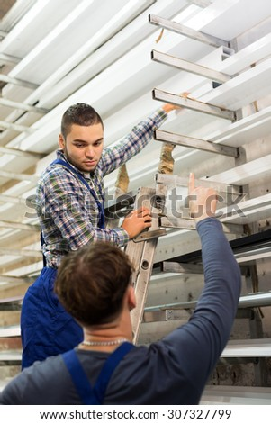 Two workers choosing PVC window profile at stand indoor - stock photo