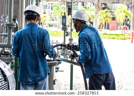 two workers cleaning filter of strainer - stock photo