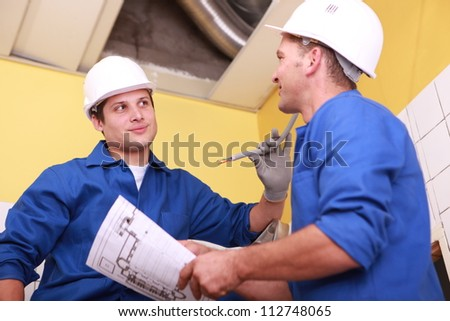 two workers dressed in blue jumpsuits in a house under construction, one of them is taking a drawing - stock photo