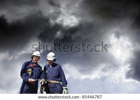 two workers, engineers, walking under a dark cloudy sky, industrial clouds conceptual shot. - stock photo