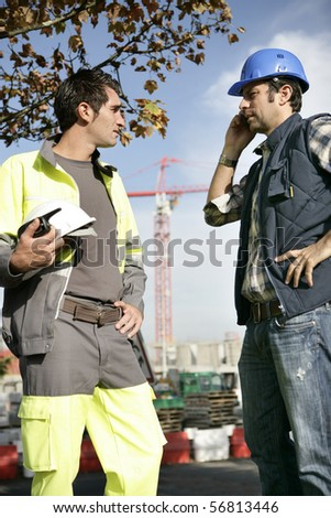 Two workers face to face on a construction site - stock photo