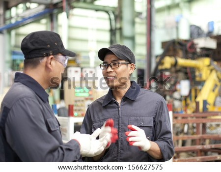 Two workers in a factory discussing how to work in factory - stock photo