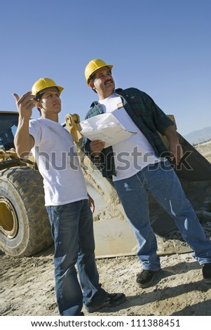 Two workers in hard hat working at construction site - stock photo