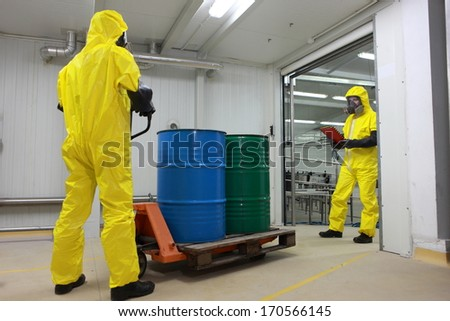 Two workers in protective uniforms,masks,gloves and boots, working with barrels of chemicals on forklift in factory - stock photo