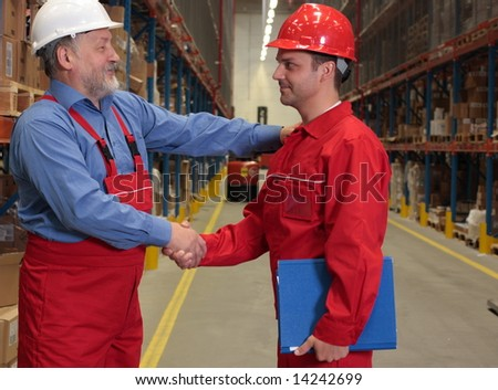 two workers in uniforms warm handshake  in warehouse.one is experienced, young is another
