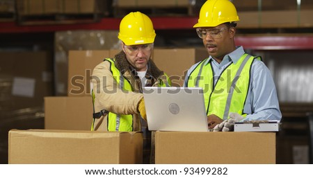 Two workers in warehouse use laptop computer - stock photo